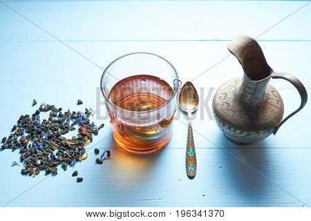 Glass Of Tea With Jug And Tea Leaves