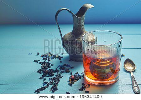Vintage Shot Of Tea Glass With Strainer, Jug, Teaspoon And Leaves