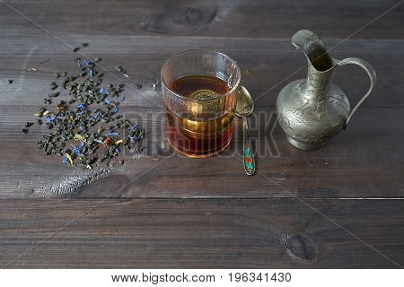 Cup Of Tea With Jug, Tea Leaves On Kitchen Desk
