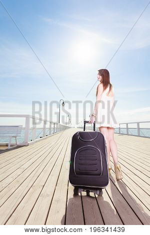 Travel adventure packing. Young woman wearing short white dress walking with suitcase on wheels through wooden pier