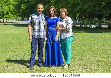 Mom, Dad and adult daughter are standing on the grass in the park zone.