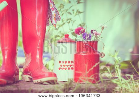 Gardening tools outdoor in garden red rubber boots and pots