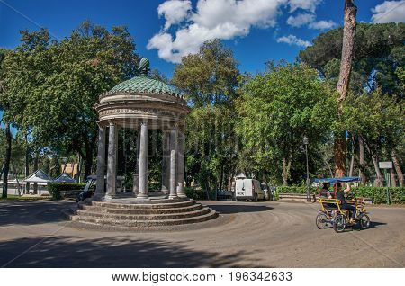Roma, Italy - May 19, 2013. View of small temple and cyclists at Villa Borghese in Rome, the incredible city of the Ancient Era, known as