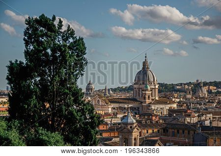 Overview of trees, cathedrals domes and buildings roofs in the sunset of Rome, the incredible city of the Ancient Era, known as