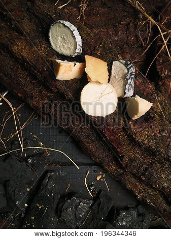 Different kinds of cheeses lie on a tree bark on a black wooden table. Pieces of black coal and hay are lying on the surface of the table.