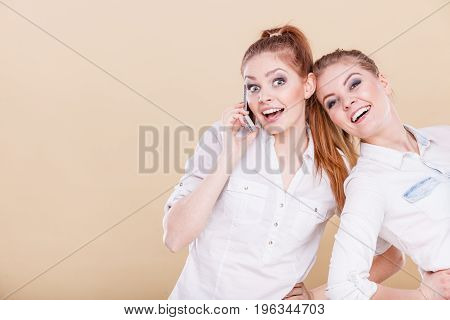 Technology communication and friendship concept. Smiling teen girls using mobile phone talking having fun positive emotional face expression