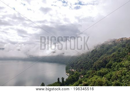 View of the slopes, forests and houses of Lake Albano on a cloudy and foggy day. Albano is a quiet and bucolic countryside region near Rome. Located in the Lazio region, central Italy