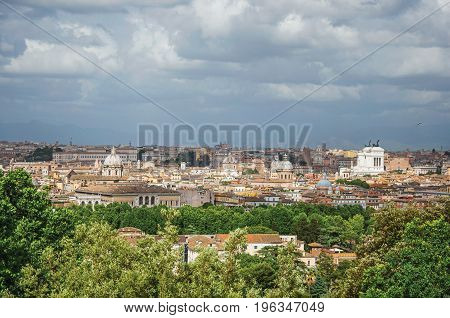 Overview of trees, cathedrals domes, monuments and roofs on a cloudy day at Rome, the incredible city of the Ancient Era, known as