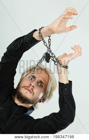 No freedom social problems concept. Sad man with chained hands studio shot on light grey background