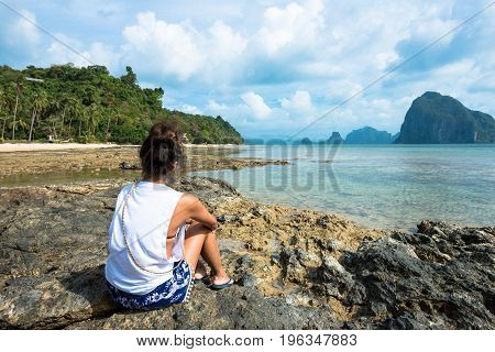 Back of tan skin woman looking the amazing view from the rocks at Las Cabanas Beach Philippines.