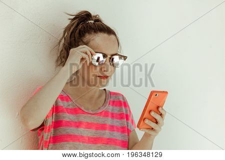 Young modern girl with sunglasses using her cellphone