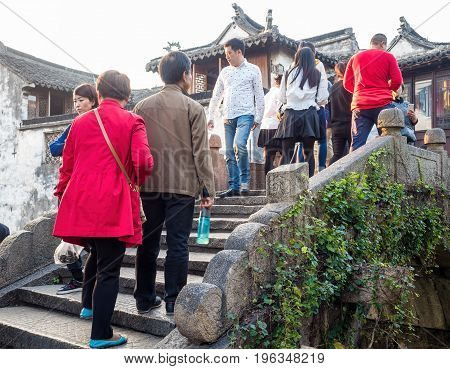 Suzhou, China - Nov 5, 2016: Many visitors crossing through an ancient arch bridge at the historic Zhouzhuang Water Town.