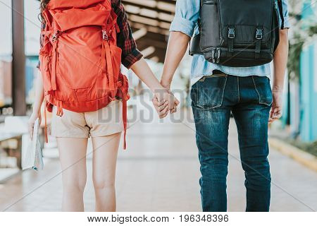 Back view of young traveler couple with backpack holding hand at train station. Travel and adventure concept