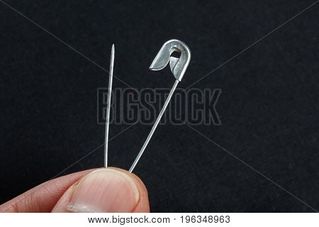 sewing safety pin on a black background