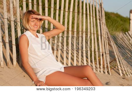 Woman Sitting On Sand At The Beach Looking The Sunset