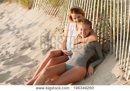 Two Beautiful Young Girls Sitting On The Beach At The Sunset