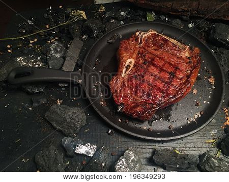 Fried steak in a frying pan with a matte surface. Pieces of coal and hay with leaves lie on the surface of the table.