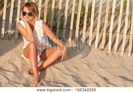 Beautiful woman sitting on sand at the beach looking the sunset