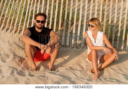Happy Friends Sitting On Beach Enjoy Sunset And Romantic Atmosphere.