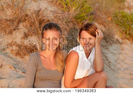 Two Beautiful Women Sitting On Sand At The Beach Look At The Sunset