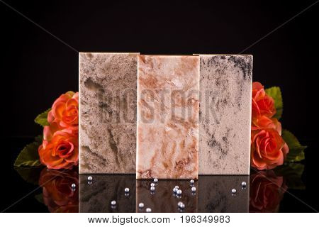 Three beautiful modern stone samples for kitchen countertop or floor tiles, decorated with flowers on  black glossy surface