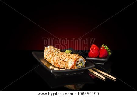 Japanese fresh sushi dragon rolls inside brownish palate decorated with strawberries and chopsticks on black table, with red light in background