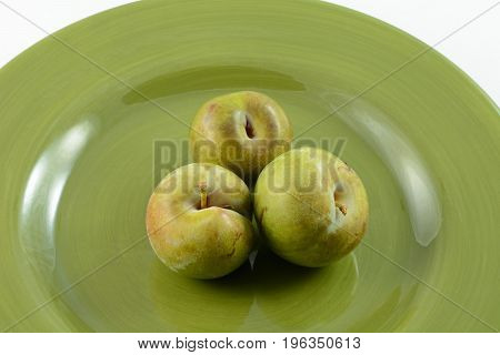 Apricot and plum hybrid plums on green plate