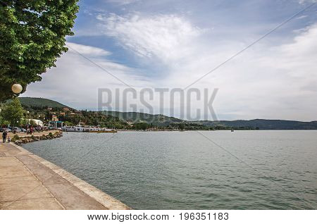 Overview of the hamlet and its promenade on the shores of Lake Trasimeno, a quiet and picturesque lake near Perugia. Located in Umbria region, central Italy
