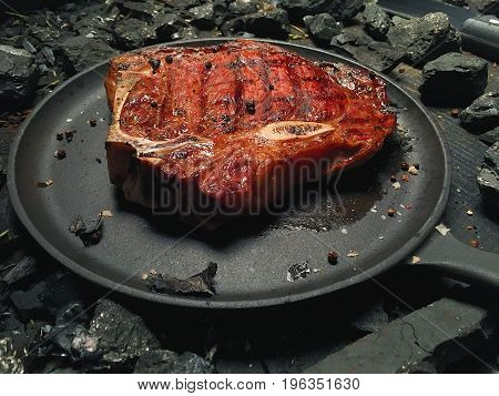 Portrait of fried steak in a frying pan among pieces of coal. A fried steak with spices lies on a plate. A juicy roasted steak lies in a frying pan on a black table. View of fried steak on a black matte frying pan.