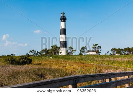 Bodie Island lighthouse and surrounding buildings on the Outer Banks of North Carolina near Nags Head, with wooden fencing in the foreground.