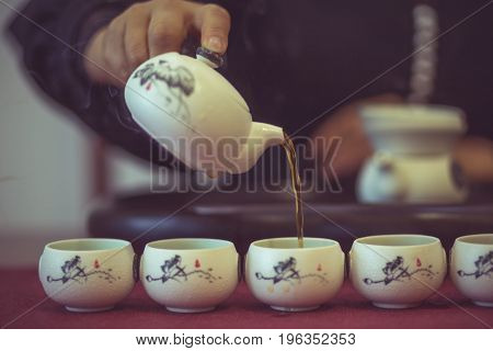 detail shot of man serving Chinese tea into ceramic tea cups.