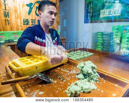 Suzhou, China - Nov 5, 2016: At the historic Zhouzhuang Water Town. Vendor moving quickly to work dough into mold for manual confectionery production. Low-light image.