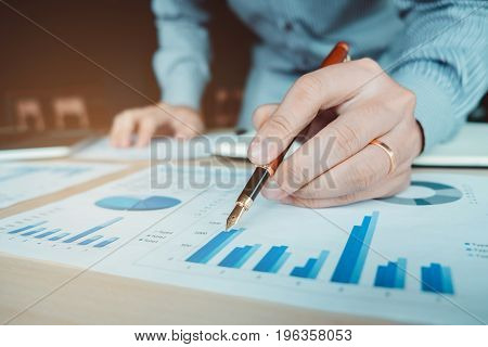 Business Hand With A Pen Pointing On The Business Paper. Report Chart
