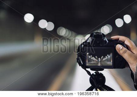 Man holding camera press shutter on tripod on subway tunnel with light bokeh