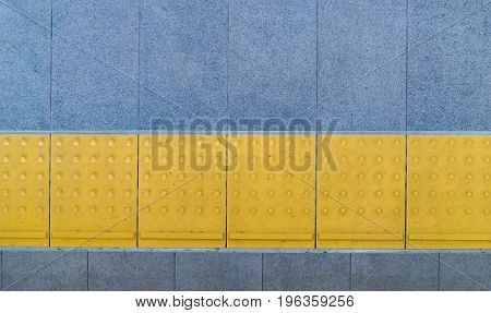 Yellow tactile paving for blind handicap on tiles footpath.