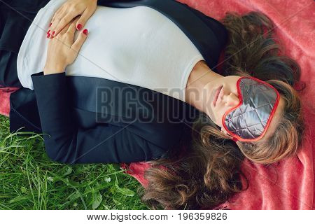 Young stylish business lady in formal trendy suit is sleeping or having nap on the red blanket in the public park. keeping hands on her tummy. Pregnant female touching her belly relaxing in open air