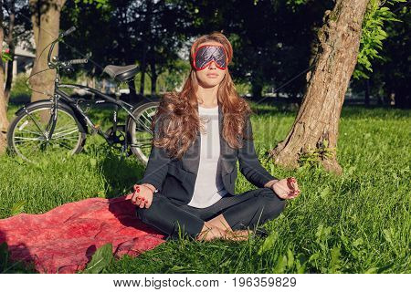 Portrait of young European businesswoman having walk in open airmeditating with closed eyes sun playing in her curly hair. Pretty woman with red nails dreaming enjoying good sunny weather outdoors