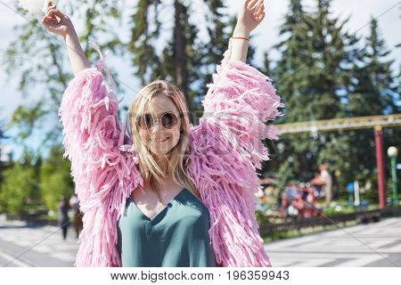 Close up shot of young Caucasian female student wearing pink coat smiling at camera with happy face expression dreaming and enjoying warm summer windlaughing and dancing alone with hands up in air.