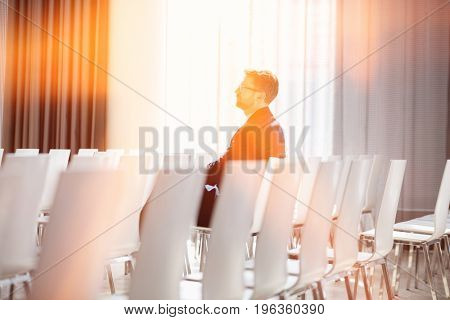Side view of businessman sitting in seminar hall