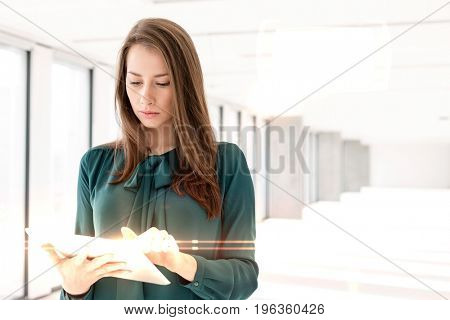 Beautiful young businesswoman using tablet computer in new office