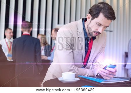 Businessman using smart phone while coffee break in convention center
