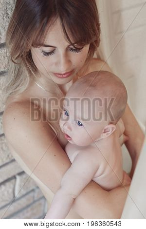 Young mother looking at her little blue-eyed baby wearing nothing relaxing and playing in the bedroom at the weekend together lazy morning warm and cozy scene. Brick wall background.