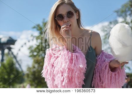 Close up portrait of happy blond female hipster wearing sunglasses greenery dress and bright coat eating white cotton candy outdoors in amusement park . Youth travel adventure vacation concept.