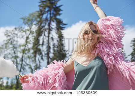 Caucasian blond student girl with cotton candy in hand wearing pink funky coat and round sunglasses resting in city park after lectures at universitylooking at camera with cheerful dreamy smile.