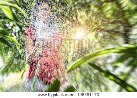 woman watering tropical garden plants blurred image