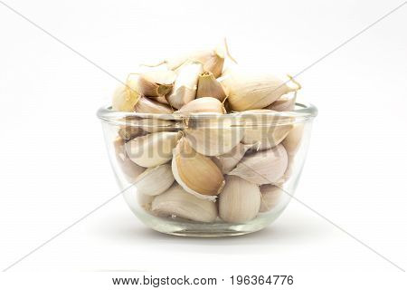 Glass cup of fresh rood gralic on white background