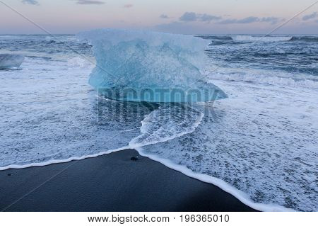 Glacial Ice breaking on black sand beach Iceland winter natural landscape background