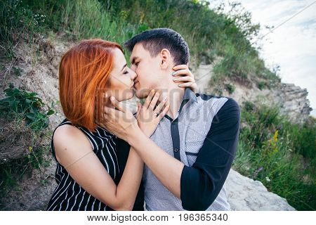 The girl kissing boy with gentle kiss, outside