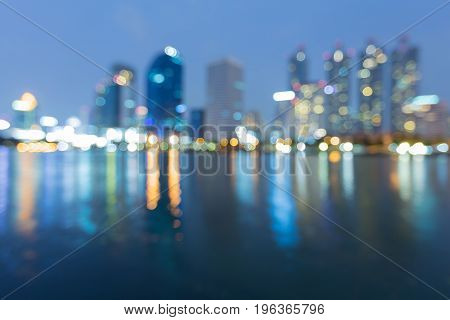 Twilight night view office building with reflection over water lake abstract background