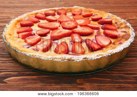 Tart with fresh strawberry on wooden background. Traditional summer dessert.